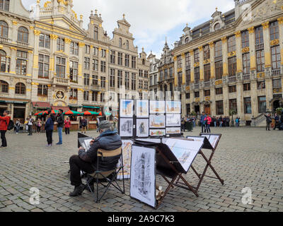 Street artist selling city centre scenes in Grand Place, Brussels, Belgium - Stock Photo