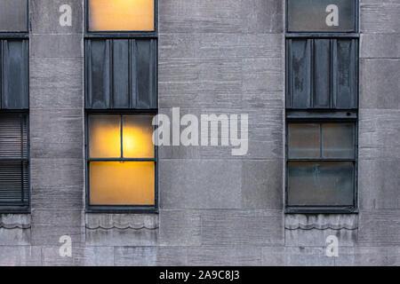 symmetrical windows, one lit and one dark on urban buildings - Stock Photo