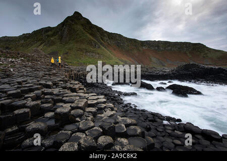 Mother and son standing on pile of rock columns formation at Giant's Causeway, Co. Antrim, Northern Ireland