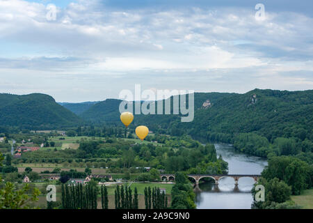 Two yellow hot air ballons flying over the Dordogne river with chateau castlenaud in the background Dordogne France - Stock Photo