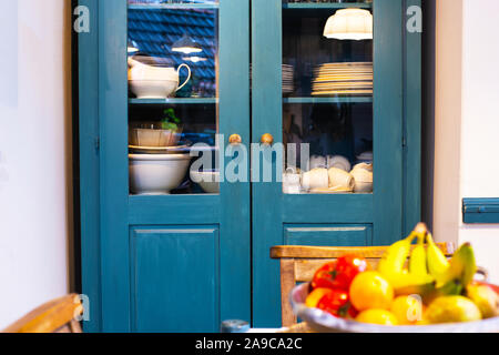 Different white dishes in cupboard in the kitchen vintage design with blue colors - Stock Photo