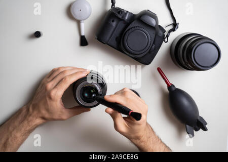 High Angle View Of Man Cleaning Camera Lens Element - Stock Photo