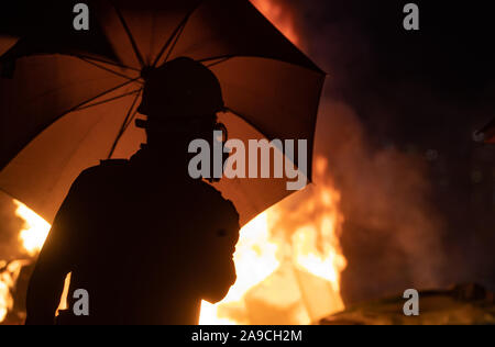 Student with an umbrella and a gas mask close to a burning barricade during the demonstrations.An unprecedented battles at Chinese University Hong Kong (CUHK) as Hong Kong protests continue for the fifth month. A citywide strike called for started on 11 November, 2019 and brought parts of Hong Kong to halt as MTR stations closed and multiple roadblocks were erected. - Stock Photo