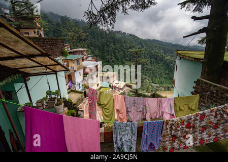 View of houses hugging the hillside in Shimla constructed close to each other. In the foreground clothes are being dried - Stock Photo