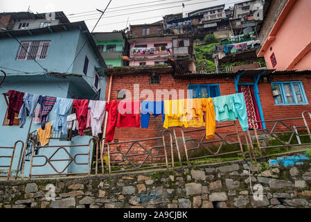 View of houses hugging the hillside in Shimla are constructed close to each other. In the foreground clothes are being dried - Stock Photo