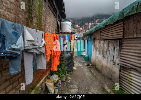 View of a street in Shimla showing clothes drying and water containers outside homes amidst heavy monsoons and water shortage - Stock Photo