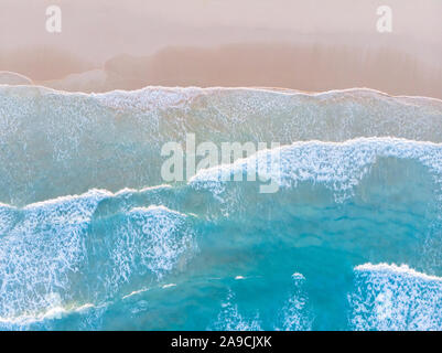 Ocean beach aerial top down view with blue water, waves with foam and spray and fine sand, beautiful summer vacation holidays destination - Stock Photo