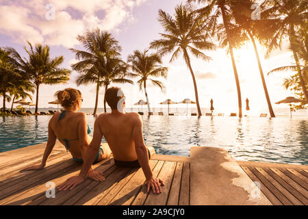 Couple enjoying beach vacation holidays at tropical resort with swimming pool and coconut palm trees near the coast with beautiful landscape at sunset - Stock Photo