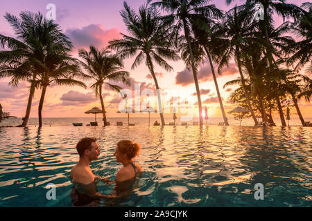 Couple at beach vacation holidays resort relaxing in swimming pool with scenic tropical landscape at sunset, romantic summer honeymoon island destinat - Stock Photo