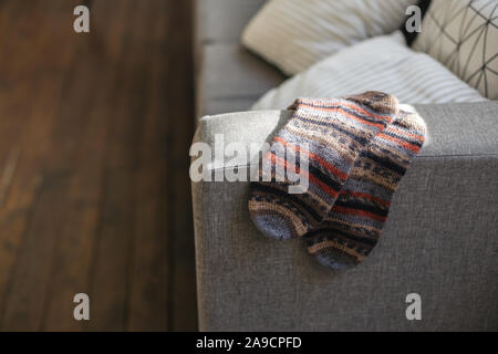 Pair of hand knitted socks on the sofa in modern interior. Natural colors. - Stock Photo