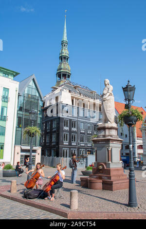 Two girls playing violin with Roland Statue and building of the Brotherhood of Blackheads, one of the most iconic buildings of Old Riga, Latvia - Stock Photo