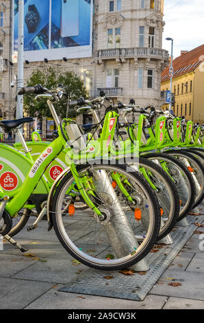 Budapest, Hungary - Nov 6, 2019: Public green bikes for rental in the center of the Hungarian capital city. Bike-sharing. Eco-friendly mean of transport. Ecological measures in the cities. Bicycle. - Stock Photo