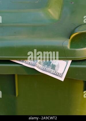 Money in trash bin - Stock Photo