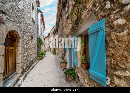A typical narrow street with French Blue shutters in the medieval village of Tourette Sur Loup in the Alpes Maritimes section of Southern, France - Stock Photo