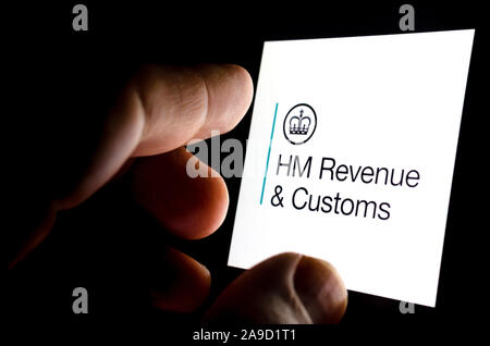 HMRC app logo on a glowing smartphone screen and the finger touching it. Conceptual photo for citizen's interaction and contact with HMRC.