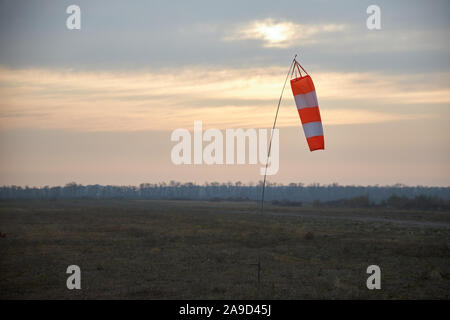 Indicator of speed and wind strength at the aerodrome in the form of a conical striped sleeve. - Stock Photo