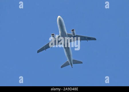 Air France Airbus A319-111 passenger jet F-GRHF flying overhead, set against a blue sky - Stock Photo