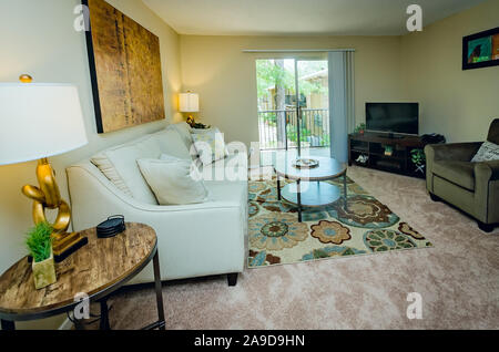 An apartment living room features a sliding glass door leading to the balcony at Autumn Woods apartment homes in Mobile, Alabama. - Stock Photo