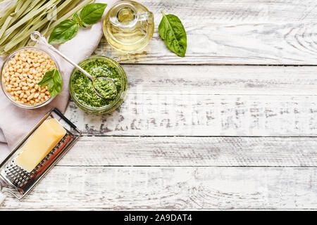 Raw green fettuccine and Pesto sauce with ingredients on rustic white wooden table. Traditional Italian pesto recipe for making fettuccine. Top view, - Stock Photo