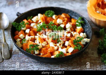 Salad with baked pumpkin and feta. Thanksgiving salad. Autumn keto salad. Keto diet. Selective focus. Macro.