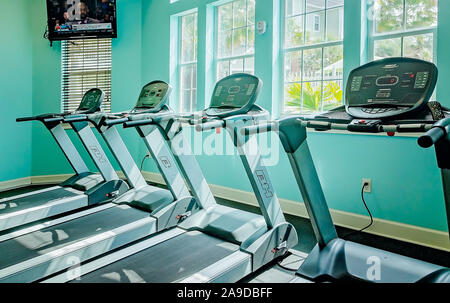 A variety of equipment, including treadmills, is available at the fitness center at Cypress Cove Apartment Homes in Mobile, Alabama. - Stock Photo