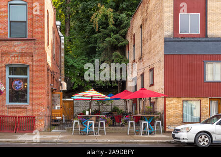 A small cafe patio with colorful umbrellas is sandwiched between two brick buildings in the historic town of Wallace, Idaho. - Stock Photo