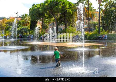 A young boy with a hat plays and splashes in the Promenade du Paillon Park in the touristic old town area of Nice, France on the French Riviera. - Stock Photo