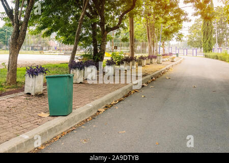An old green dustbin in the public park beside the walk way for protect environment. - Stock Photo