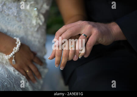 Bride and groom holding hands showing off their wedding rings - Stock Photo