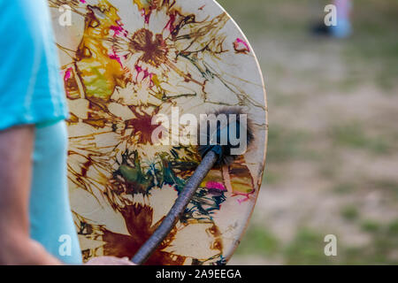 A selective focus and close-up view of a person's hand holding a traditional native drum and drumstick, playing native American sacred music - Stock Photo