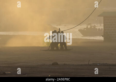 Military team in conflict rescuing people by helicopter. Getting loaded on a rope attached to chopper in the smoke and haze in the Middle East conflict - Stock Photo