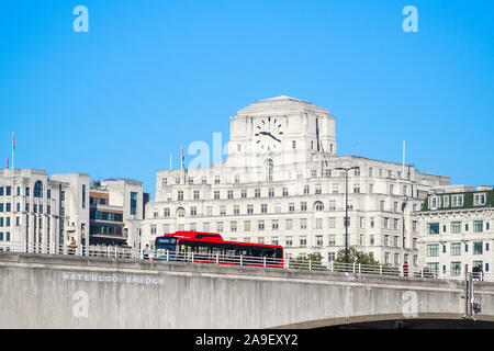 Waterloo Bridge with a passing bus and facade of Shell Mex House in the background in London - Stock Photo