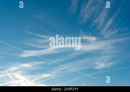 Abstract sky background with airplane contrail, trail and light clouds. Minimalistic nature background - Stock Photo