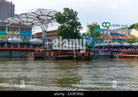 Singapore, Singapore - October 4, 2013: Clarke Quay historical riverside quay and old historic cruise boats on sunny day - Stock Photo