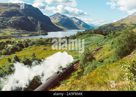 The Jacobite Steam Train, also known as the Hogwarts train as it was used in the Harry Potter movie franchise, traveling along the Glenfinnan Viaduct - Stock Photo