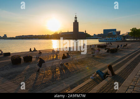 Stockholm Sweden, view of people in summer relaxing on the waterfront terrace of Riddarholmen watching the sun set over Kungsholmen, central Stockholm. - Stock Photo