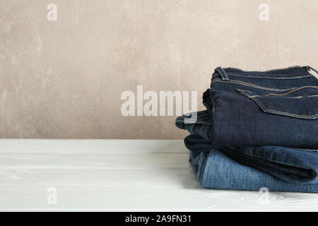Stack of jeans pants on white background, space for text - Stock Photo