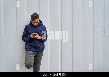 Teen with mobile phone on a white wall - Stock Photo