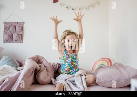 young girl stretching and yawning in the morning in her bed at home - Stock Photo