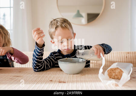 young boy during milk on his breakfast at home before school - Stock Photo