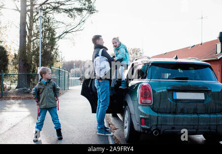 father dropping his kids off at school in the morning - Stock Photo