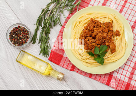 Porcelain plate with spaghetti bolognese on kitchen napkin. Spices, bottle of oil and rosemary on wooden boards. Top view. - Stock Photo