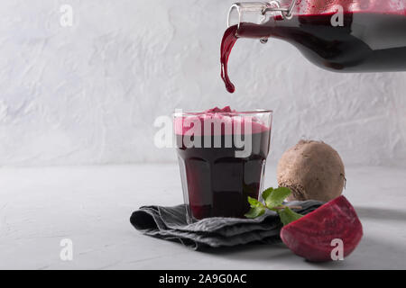 Pouring beetroot juice from bottle to glass. Close up. Space for text. Healthy detox beverage. - Stock Photo