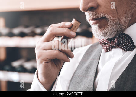 Sommelier Concept. Senior man standing smelling wine cork close-up - Stock Photo