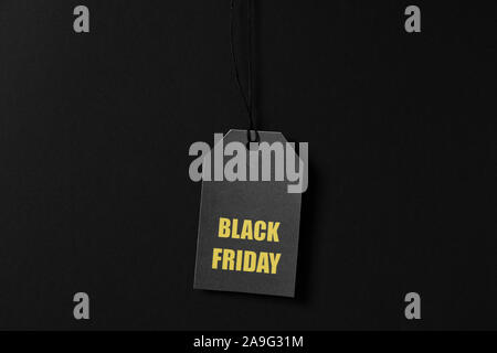 Inscription Black Friday on price tag on black background, copy space - Stock Photo