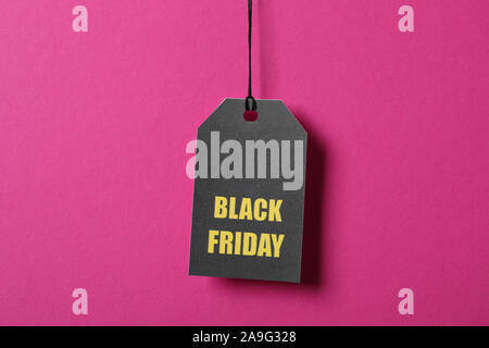 Inscription Black Friday on price tag on pink background, copy space - Stock Photo