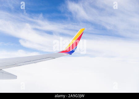 Looking out a Southwest airplane window in flight to see the wing, blue sky, and clouds. - Stock Photo