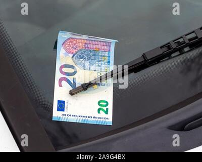 Lost and found money attached under car windshield rain wiper - Stock Photo