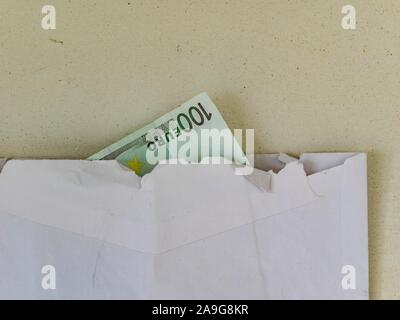 Money in paper envelope with hard-jagged edge - Stock Photo
