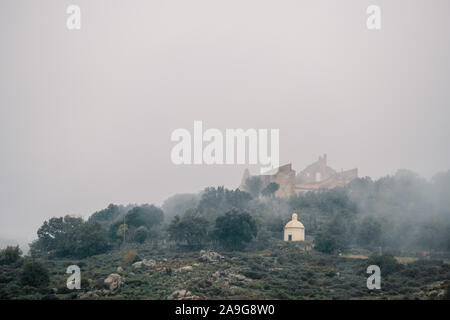 The ancient Couvent Santa Maria di a Pace and a mausoleum shrouded in mist in the ancient mountain village of Speloncato in the Balagne region of Cors - Stock Photo